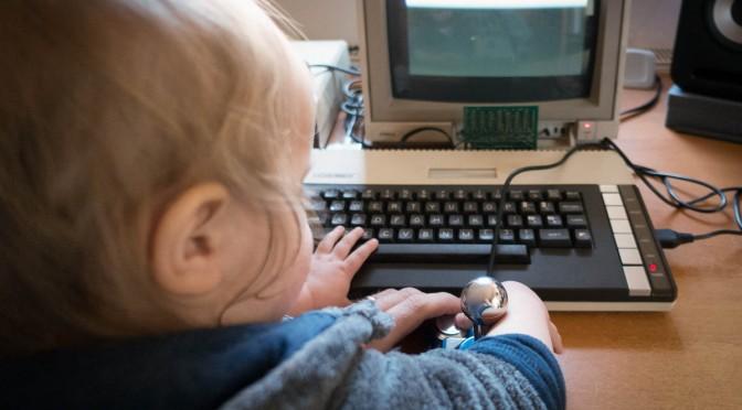 Kleinkind sitzt an einem alten 8-Bit-Computer und drückt einen Joystick-Knopf