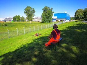 Ein Mann in Orange fernsteuert einen Rasenmähroboter